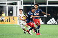 FOXBOROUGH, MA - MAY 22: Caden Clark #37 of New York Red Bulls and Brandon Bye #15 of New England Revolution turn to chase down a ball in the midfield during a game between New York Red Bulls and New England Revolution at Gillette Stadium on May 22, 2021 in Foxborough, Massachusetts.