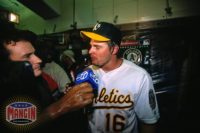 OAKLAND, CA - Jason Giambi of the of the Oakland Athletics gets interviewed in the A's clubhouse after the A's clinched the American League Western Division crown in 2000. (Photo by Brad Mangin)