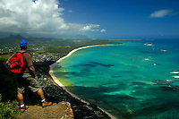 A hiker stops to enjoy this panoramic view of Waimanalo Bay and it's white sand beaches from the Tom-Tom trail above Sea life park, windward Oahu.
