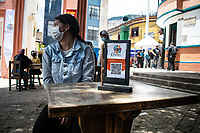 "BOGOTA - COLOMBIA, 05-09-2020: Un comensal espera durante el primer día del piloto de apertura de restaurantes y cafés al aire libre, denominado ""Bogotá a Cielo Abierto"", en el Chorro de Quevedo en el centro de Bogotá que ahora tiene sus calles pintadas con formas geométricas en pintura neón y cuenta con mesas, distribuidas estratégicamente para mantener el distanciamiento físico al finalizar la cuarentena total en el territorio colombiano causada por la pandemia  del Coronavirus, COVID-19. / A dinner waits during the first day of the pilot for the opening of restaurants and outdoor cafes, called ""Bogotá a Cielo Abierto"", in Chorro de Quevedo in the center of Bogotá, which now has its streets painted with geometric shapes in neon paint and has tables, strategically distributed to maintain physical distancing at the end of the total quarantine in the Colombian territory caused by the Coronavirus pandemic, COVID-19. Photo: VizzorImage / Johan Rugeles / Cont"