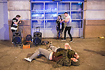 © Joel Goodman - 07973 332324 . Manchester , UK . 05/04/2015 . Two men lie on the pavement on Withy Grove in Manchester City Centre as a beat-boxing duo perform . Revellers on a Saturday night out during the Easter Bank Holiday weekend . Photo credit : Joel Goodman