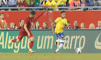 Brazil forward Neymar (10) dribbles down the wing.  In an international friendly, Brazil (yellow/blue) defeated Portugal (red), 3-1, at Gillette Stadium on September 10, 2013.