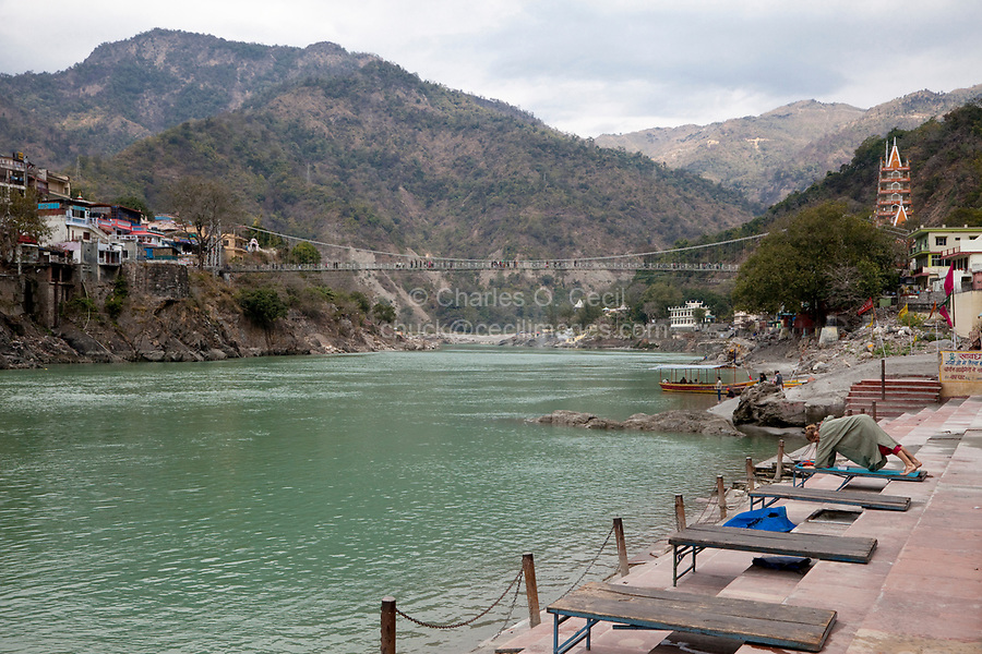India, Rishikesh.  Ganges (Ganga) River, looking upstream toward the Himalayas. Yoga practitioner in foreground.  Suspension footbridge linking the two banks in background.