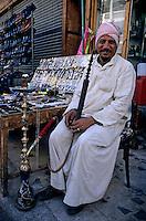 Market vendor smoking a hookah in the bazaar, Aswan, Egypt.
