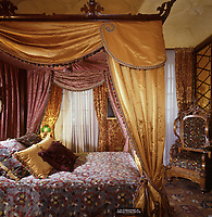 The guest bedroom is furnished with a Chippendale four-poster bed, draped in yellow silk and lined with damask