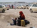 Iraq 2013 .Near the entrance of Domiz Refugee Camp,a woman with her child arriving from the Syrian border.Irak 2013 .A l'entree du camp de refugies de Domiz, de nouveaux arrivants, une femme avec son enfant en provenance de la frontiere syrienne
