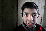 A boy who lived in a Roma settlement under a highway bridge in Belgrade, Serbia, in February 2012. The families that lived here, most of whom survive from recycling cardboard and other materials, were forcibly evicted in April 2012. Many were moved into metal shipping containers on the edge of Belgrade..
