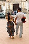 Guatemalan couple walk hand in hand near the main plaza in Antigua, Guatemala