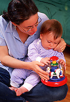 Mother and infant child play with a toy