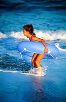 A young girl plays with an inner tube on the beach as waves wash in to shore.