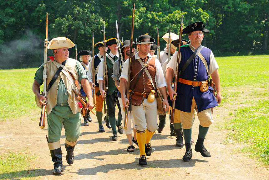 Militiamen, citizens recruited for State defense, march off the field of battle after a reenactment with British redcoats at the Nathan Hale Homestead during a Revolutionary War encampment and muster, Coventry, Connecticut, USA.