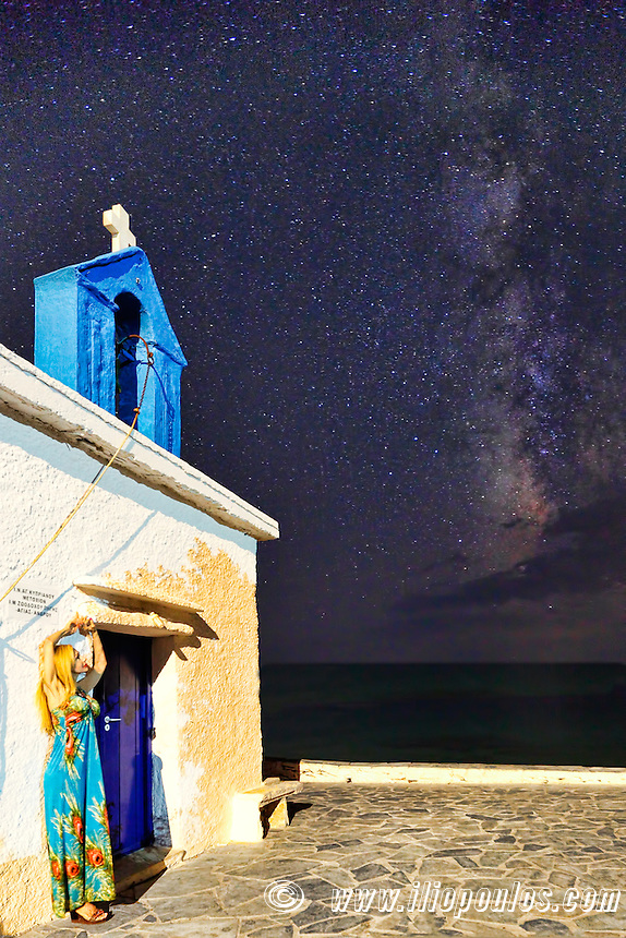 A woman in front of a Greek chapel under the Milky Way