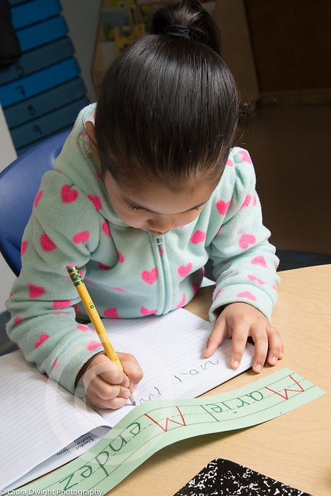 Education Preschool Childcare 2-3 year olds girl writing her name at start of day, using printed name card as a guide