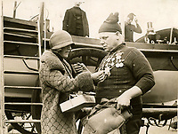 BNPS.co.uk (01202 558833)<br /> Pic: RNLI<br /> <br /> Pinning badge onto a highly decorated crew member, 1925.<br /> <br /> Splash in the Attic...<br /> <br /> A 'lost' cache of 13,000 photographs charting the history of the RNLI has been found in the attic of the charity's headquarters.<br /> <br /> Many of the black and white photos date back to the 1920s and '30s long before the terms 'health and safety' and 'risk assessment' were thought of.<br /> <br /> One image depicts a brave lifeboatman dressed in a suit and cloth cap just as the lifeboat he is on launches down a ramp into a choppy sea.<br /> <br /> Another shows the crew of another open lifeboat getting swamped by waves with only their souwesters and lifejackets to protect them.<br /> <br /> The photos have been unearthed in storage space at the RNLI HQ in Poole, Dorset, and they are now being digitised.