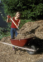Happy woman pitching compost into wheelbarrow from large pile