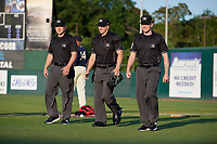 Umpires Matthew Bates, Mark Stewart, and Matt Winter (L-R) walk to home plate before a Southern League game between the Jacksonville Jumbo Shrimp and Mobile BayBears on May 7, 2019 at Hank Aaron Stadium in Mobile, Alabama.  Mobile defeated Jacksonville 2-0.  (Mike Janes/Four Seam Images)