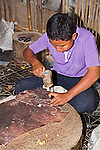 Young Cambodian male student creates ancient elephant design out of leather with hammer and nail in shop to learn traditional ancient handicraft