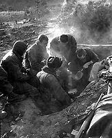 These men of the Heavy Mortar Co., 7th Inf. Regt., go native, cooking rice in their foxhole in the Kagae-dong area, Korea.  December 7, 1950.  Pfc. Donald Dunbar.  (Army)<br /> NARA FILE #  111-SC-354103<br /> WAR & CONFLICT BOOK #:  1472