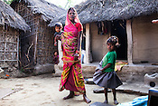 28 year old Asha Devi seen with her daughters - 11 month old Sharda and 4 year old Radha in the courtyard of their house in Saptari, Nepal. <br /> Asha Devi got married when she was 14. She got pregnant after 6 months of her marriage. Her first child survived for 6 days, she woke up next to a dead baby. She was pregnant two months later. Asha Devi's 2nd daughter survived for 9 months and later died due to prolonged fever. 3 months after her daughter died, Asha was pregnant again and within w months, she had spontaneous abortion. She was pregnant with Radha Kumari mandal who was acutely malnourished. Radha was admitted when she was 36 months old on October, 20th 2013. MUAC - 110 mm, Weight - 7 kg, Height - 75 cm. Radha was discharged on Dec 6, 2013 - her MUAC at the time of discharge was 128mm, Weight 8.8kg and height- 75.5 cm. She consumed 100 sachets of RUTF and gained 5gm/day while on the programme. <br /> Rukmini, her second daughter was born a year after Radha was born. Rukmini was severely malnourished too. She was admitted on Feb 16th, 2014. Her MUAC was 119mm, weight - 11 kg, and height - 96 cm. Her third daughter Sharda is severely malnourished. Sharda is under RUTF.  <br /> Asha Devi is pregnant for the 7th time and is 6 months pregnant.