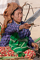 Myanmar, Burma.  Woman of Pa-O Ethnic Group at Local Market, Inle Lake, Shan State, Handing Change to a Customer.  She has remnants of thanaka paste on her face, a natural cosmetic sunscreen.