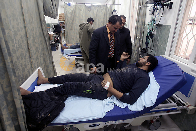A Palestinian medic treats a man whom they said was wounded in an Israeli air strike, at a hospital in Rafah in the southern Gaza Strip March 13, 2014. Egypt brokered a ceasefire on Thursday aimed at ending a flare-up of rocket attacks from Gaza on Israeli towns and Israeli air strikes in the Palestinian enclave, the Islamic Jihad militant group said. Photo by Eyad Al Baba