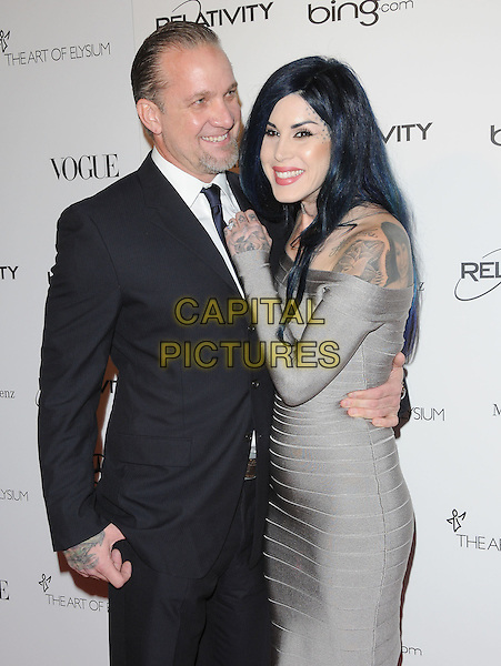 """JESSE JAMES & KAT VON D .attends the Art of Elysium 4th Annual Charity Gala """"Heaven"""" held at The Annenberg Building at The California Science Center in Los Angeles, California, USA, January 15th 2011..half length black suit tie couple arm around  grey gray herve leger bandage dress  tattoos off the shoulder long sleeve                                      .CAP/RKE/DVS.©DVS/RockinExposures/Capital Pictures."""