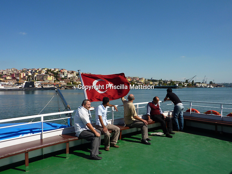 Istanbul, Turkey - September 23, 2009:  Men take in the view from a boat on the Bosphorus.