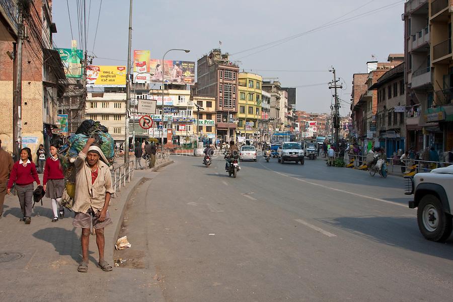 Kathmandu, Nepal.  Street Scene.  School Girls in Uniform.  Laborer Carrying Heavy Load.  Traffic.