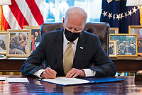 United States President Joe Biden signs the PPP Extension Act of 2021 into law in the Oval Office of the White House in Washington, DC, Tuesday, March, 30 2021.<br /> CAP/MPI/RS<br /> ©RS/MPI/Capital Pictures