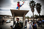 A Jewish settler dressed as a clown juggle on top of an Israeli checkpoint during Purim parade at the West Bank city of Hebron Sunday March 12 2017. Purim is a Jewish holiday that commemorates the saving of the Jewish people in ancient Persia , the story is recorded in the Biblical Book of Esther. Photo by Eyal Warshavsky