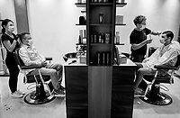 """Switzerland. Canton Ticino. Lugano. «Salone by Franco» is a hairdressing salon. A man and a woman, both stylists, wear a mask on their faces to protect themselves from the Coronavirus (also called Covid-19). They stand up and style hair to two men seated on chairs, both wearing also masks. Due to the spread of the coronavirus (also called Covid-19), the Federal Council has categorised the situation in the country as """"extraordinary"""". It has issued a recommendation to all citizens to stay at home, especially the sick and the elderly. From March 16 the government ramped up its response to the widening pandemic, ordering the closure of hairdressing salons. From April 27, they can reopen under very tight conditions with a limited number of customers. Social distancing and masks. 30.04.2020 © 2020 Didier Ruef"""
