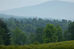 The steeple of the Sugar Hill Meetinghouse peeks above the trees in Sugar Hill, NH, USA