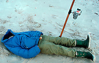 A patient and determined fisherman lies on the beach, completely tucked into his clothing in bitter cold weather.