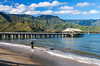A surfer looks out at Hanalei Bay, Hanalei Beach, Kaua'i.