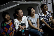 Young Chinese employees share a lighter moment at one of their colleague's dormitory in the Chinese Colony of the Adani Power Plant in Mundra port industrial city of Gujarat, India. Indian power companies have handed out dozens of major contracts to Chinese firms since 2008. Adani Power Ltd have built elaborate Chinatowns to accommodate Chinese workers, complete with Chinese chefs, ping pong tables and Chinese television. Chinese companies now supply equipment for about 25% of the 80,000 megawatts in new capacity.