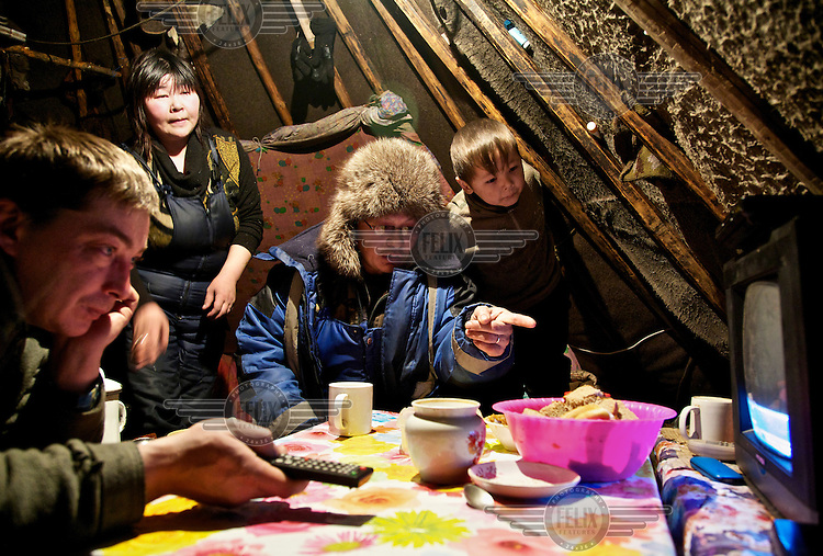 A Nenets family discuss a television programme they are watching inside their choom (tent) in Naryan-Mar. Outside it is -40 Celcius. /Felix Features