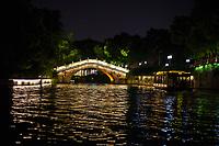 Nanjing, Jiangsu, China.  Tourist Boat on the Qinhuai River Approaching Pedestrian Bridge at Night.