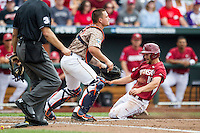 Arkansas Razorbacks outfielder Joe Serrano (10) slides safely in home as Virginia Cavaliers catcher Matt Thaiss (21) stands by in Game 1 of the NCAA College World Series on June 13, 2015 at TD Ameritrade Park in Omaha, Nebraska. Virginia defeated Arkansas 5-3. (Andrew Woolley/Four Seam Images)