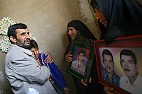 Iranian President Ahmadinejad embraces a young boy whilst visiting the family of a soldier killed during the Iran-Iraq War, as part of the programme of one of his regional tours. Two women stand holding photographs of the young man who was killed.
