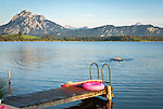 Germany, Bavaria, Upper Swabia, East-Allgaeu, Hopfen at Hopfen Lake: children swimming with surfboard, at background Allgaeu Alps | Deutschland, Bayern, Oberschwaben, Ost-Allgaeu, Hopfen am See: Kinder baden im See und spielen mit einem Surfboard, im Hintergrund die Allgaeuer Alpen