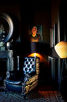 A blue leather armchair with lettered upholstery is placed in the corner of a dark sitting room. A table lamp illuminates a portrait painting on the wall.