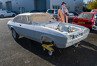 BNPS.co.uk (01202) 558833. <br /> Pic: MattRichardson/Classic Ford/BNPS<br /> <br /> Pictured: Arthur Daley, cardboard cut out, keeps an eye on the restoration process. <br /> <br /> The legendary Ford Capri that starred in '80s TV show Minder has been restored to its former glory after a devastating fire wrecked the car.<br /> <br /> The 1977 white motor which appeared on the opening titles of the comedy-drama caught ablaze while it was returning from an MoT test last year.<br /> <br /> It is thought an electrical fault in the engine bay caused the fire. <br /> <br /> Now a mechanic who specialises in classic car restorations has unveiled the famous Ford after fixing it up over the past six months.