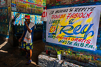 "A Colombian sign painter walks along a just-finished music party poster in the sign painting workshop in Cartagena, Colombia, 14 April 2018. Hidden in the dark, narrow alleys of Bazurto market, a group of dozen young men gathered around José Corredor (""Runner""), the master painter, produce every day hundreds of hand-painted posters. Although the vast majority of the production is designed for a cheap visual promotion of popular Champeta music parties, held every weekend around the city, Runner and his apprentices also create other graphic design artworks, based on brush lettering technique. Using simple brushes and bright paints, the artisanal workshop keeps the traditional sign painting art alive."