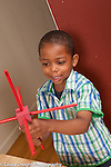 3 year old boy playing with wood cube and stick construction talking to self vertical