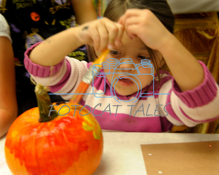 Amelia Baltazar, 4, uses paint on her pumpkin at the Carson City Library Monday, Oct. 27, 2014. As part of the library's Halloween festivities, dozens of children decorated pumpkins or gourds and took part in a costume contest.