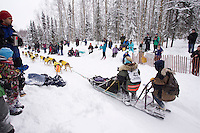 Saturday, March 3, 2012  Spectaors watch Colleen Robertia round the corner at the Goose Lake turn during the Ceremonial Start of Iditarod 2012 in Anchorage, Alaska.