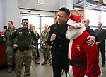 From left, Sgt. Daniel Gonzales, Gov. Brian Sandoval and Santa welcome volunteers to the 14th annual Holiday with a Hero shopping day in Carson City, Nev., on Monday, Dec. 20, 2017.<br />Photo by Cathleen Allison/Nevada Momentum