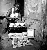 A soldier of the ROK Army eating lunch in a war-destroyed house in Munsan-ni, Korea, as a field ration made in Japan for the ROK Army is shown unpacked.  July 17, 1951.  G. Dimitri Boria. (Army)<br /> NARA FILE #  111-C-6560<br /> WAR & CONFLICT BOOK #:  1473