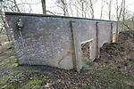 Foto: VidiPhoto<br /> <br /> SOESTERBERG – Een afgelegen herdenkingsplek, diep in de bossen van de voormalige vliegbasis Soesterberg, herinnert aan de executie van 33 Nederlandse verzetsstrijders op 19 november 1942 door de Duitze bezetter. Het enige dat ze met plek gemeen hebben, is dat ze naar deze toen Duitse vliegbasis werden getransporteerd en daar achter de schietbaan door een vuurpeloton in koelen bloede werden vermoord. Om de schoten te camoufleren vonden er op dat moment aan de voorzijde schietoefeningen plaats door Duitse soldaten. Vrijwilligers van het Nationaal Militair Museum Herman van den Berg en Adriaan van Hemert (met pet), hebben zich in deze vrij onbekend gebleven massa-executie verdiept. Foto: De stenen muur vlak bij de fussiladeplek.