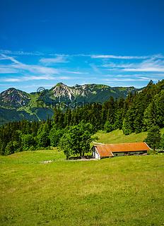 Deutschland, Bayern, Chiemgau, oberhalb von  Schleching: die Donauer Alm voir den Gipfel Breitenstein (links) und Geigelstein (rechts) der Chiemgauer Alpen, am Wanderweg gegenueber ist die Wuhrsteinalm zu erkennen   Germany, Bavaria, Chiemgau, above Schleching: alpine pasture hut 'Donauer Alm' and summits Breitenstein (left) and Geigelstein (right) of Chiemgau Alps, opposite visible alpine pasture hut 'Wuhrsteinalm'